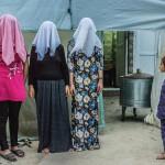 Три курдские женщины фотографируются с закрытыми лицами.