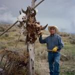 Лео Титон стоит рядом со столбом, увешенным черепами бизонов, что символизирует духовную связь между племенем шошоны и зубрами в Форт-Холл, Айдахо.